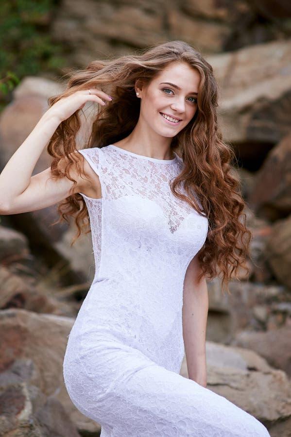 美丽的年轻新娘坐岩石 免版税库存图片