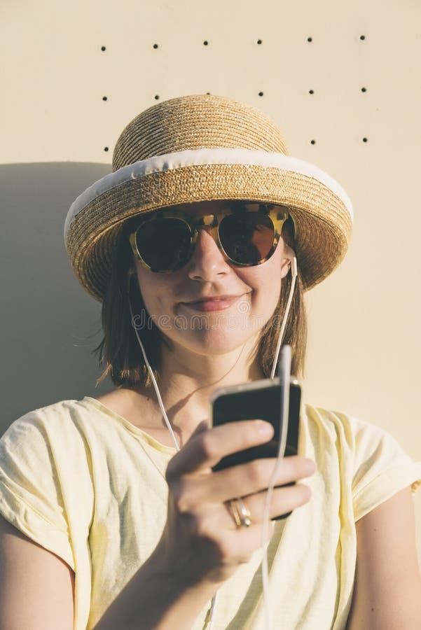 美丽的年轻有智能手机和earp的行家白种人妇女 免版税库存图片