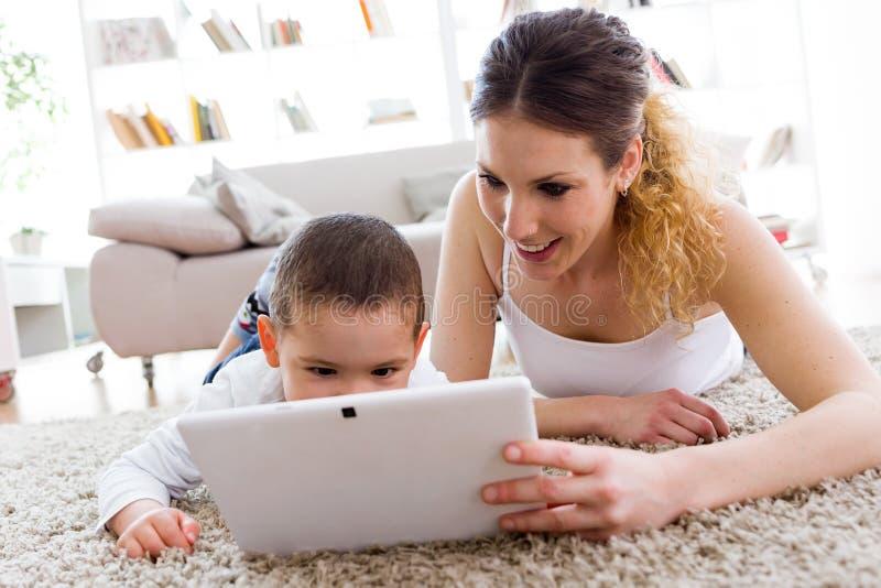 美丽的年轻母亲和她的在家使用数字式片剂的儿子 免版税库存照片