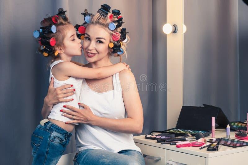 美丽的年轻母亲和她的女儿有卷发夹的 免版税库存图片