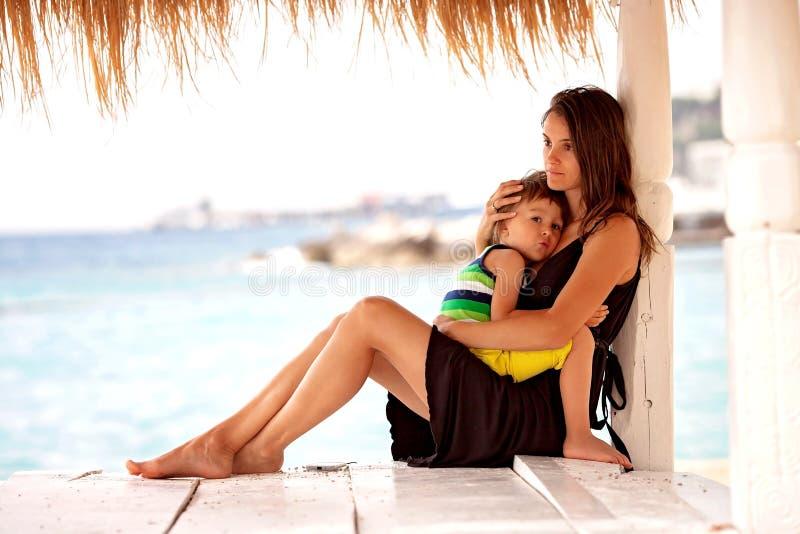 美丽的年轻母亲,拥抱她的海滩的孩子 库存图片