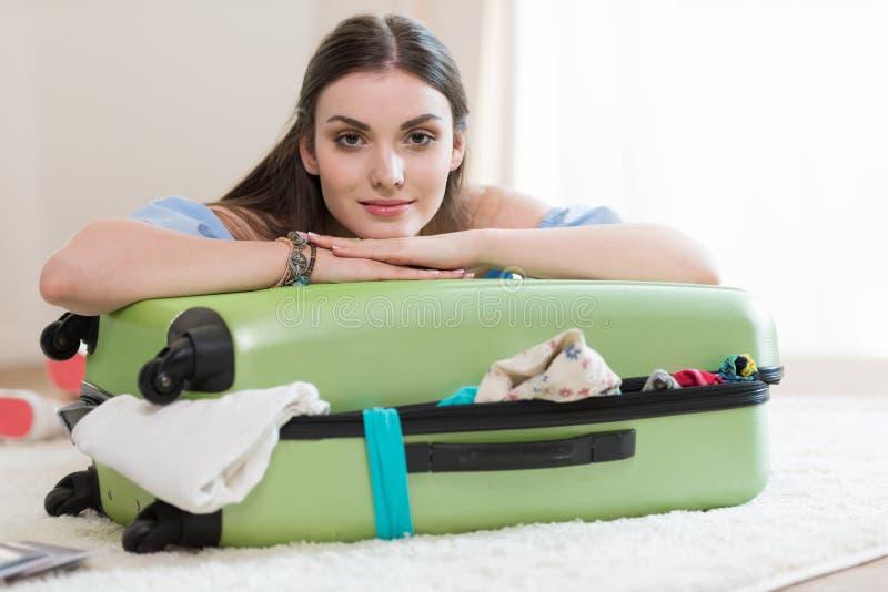 美丽的年轻深色的妇女包装手提箱和看照相机 免版税库存图片
