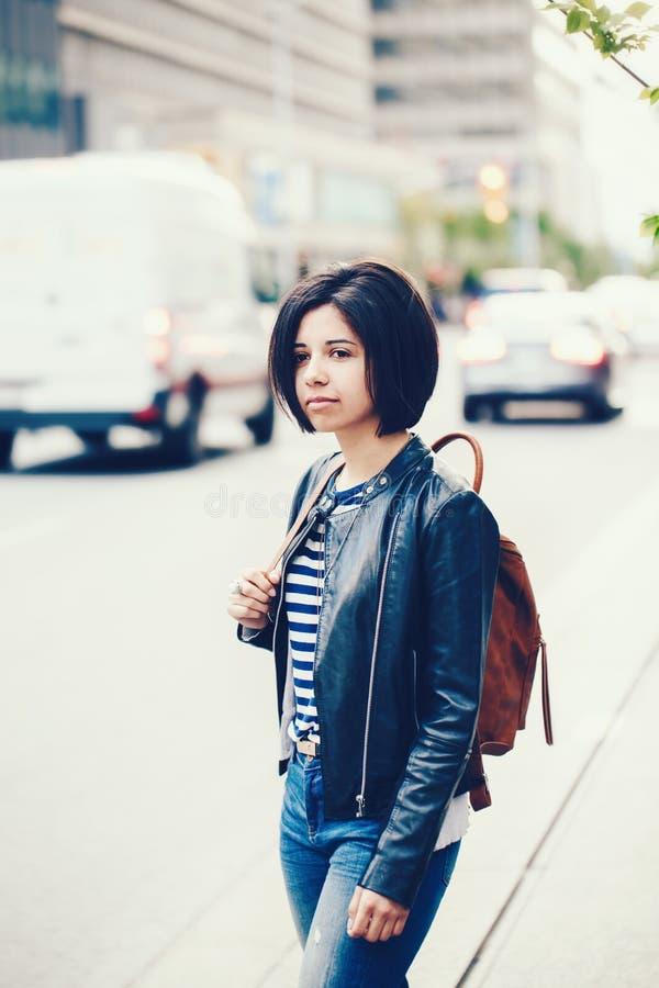 美丽的年轻白种人拉丁美州的女孩妇女画象有黑褐色眼睛和短小黑发的在蓝色牛仔裤 免版税图库摄影