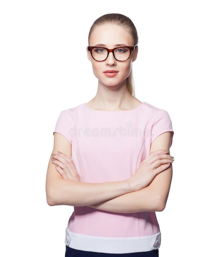 美丽的年轻白肤金发的与被交叉的双臂的妇女佩带的玻璃 办公室样式 查看照相机 背景查出的白色 图库摄影