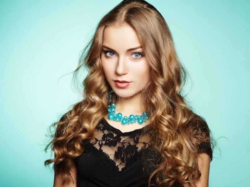 美丽的年轻白肤金发的女孩画象黑礼服的 库存照片