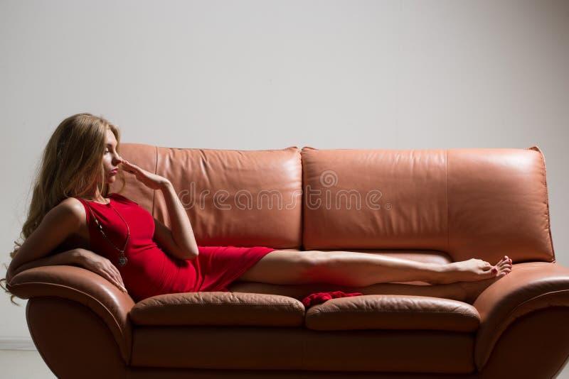 美丽的年轻白肤金发的妇女全长画象长沙发的 长期卷发 红色礼服 免版税库存图片