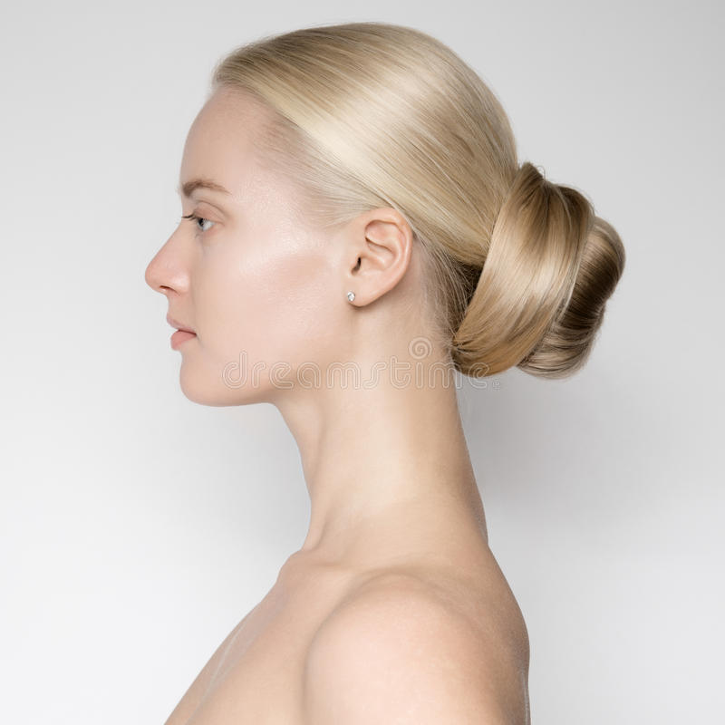 美丽的年轻白肤金发的妇女用小圆面包Hairstуle 库存照片