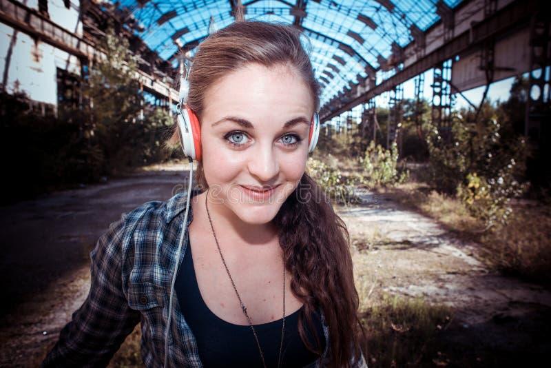 美丽的年轻白肤金发的行家妇女听的音乐 库存照片