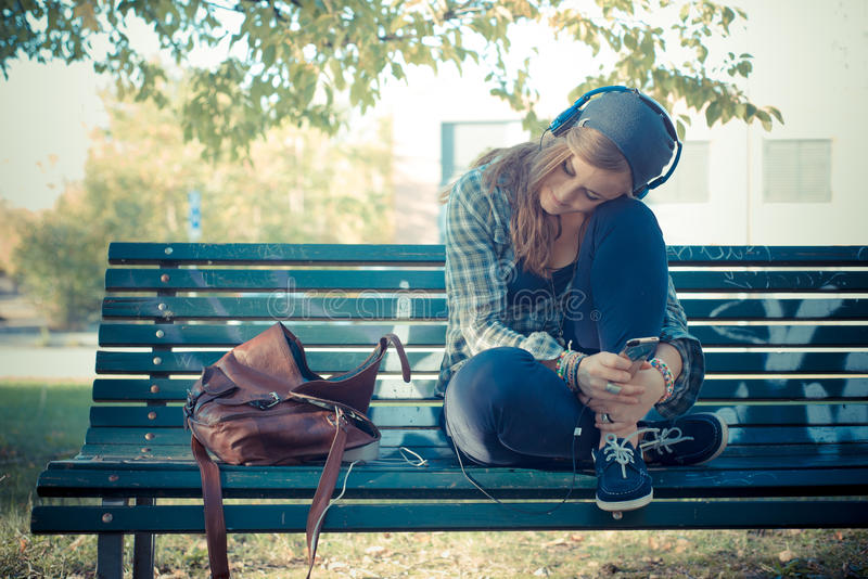 美丽的年轻白肤金发的行家妇女听的音乐 库存图片