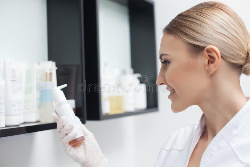 美丽的年轻美容师选择化妆用品 库存图片