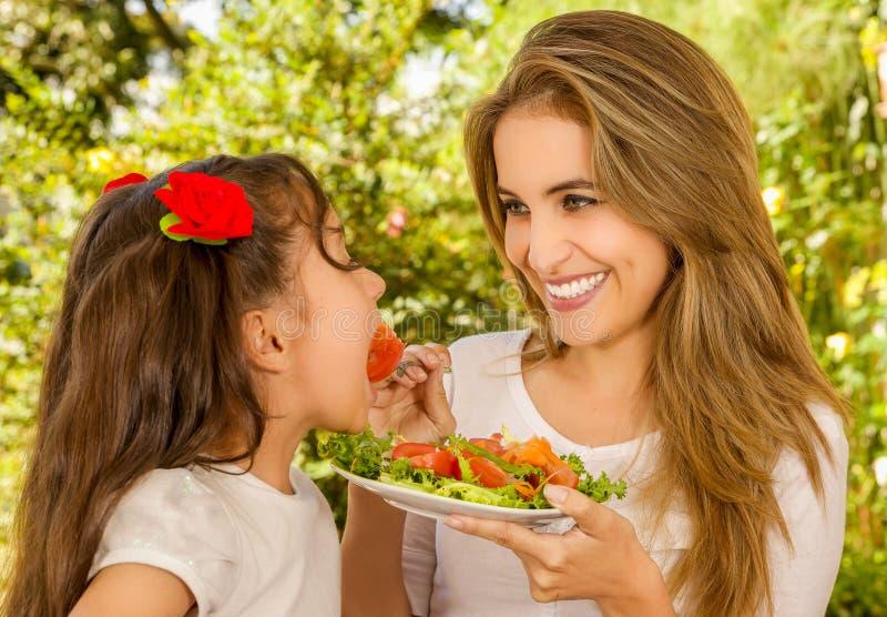 美丽的年轻获得母亲和的女儿吃健康发射的乐趣 免版税库存照片