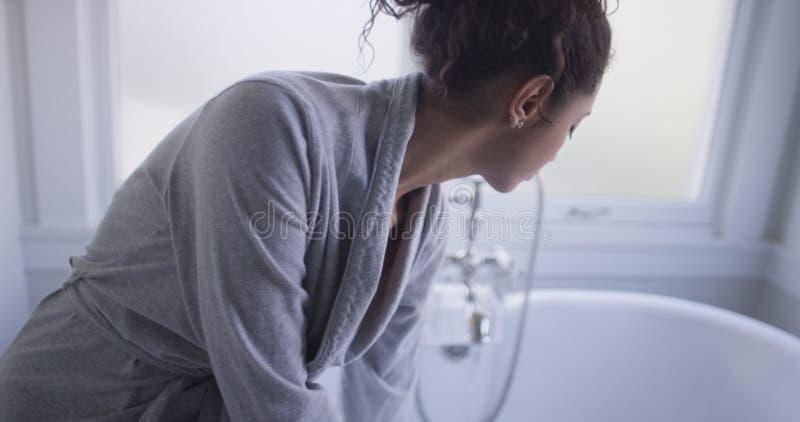 美丽的年轻西班牙妇女坐浴缸测试水 免版税库存图片