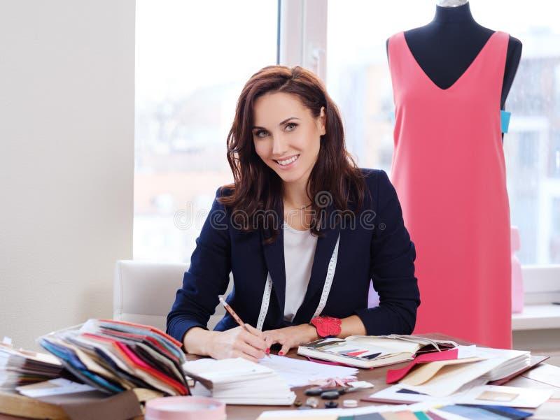 美丽的年轻设计师在她的时尚工作室陈列室里 免版税图库摄影