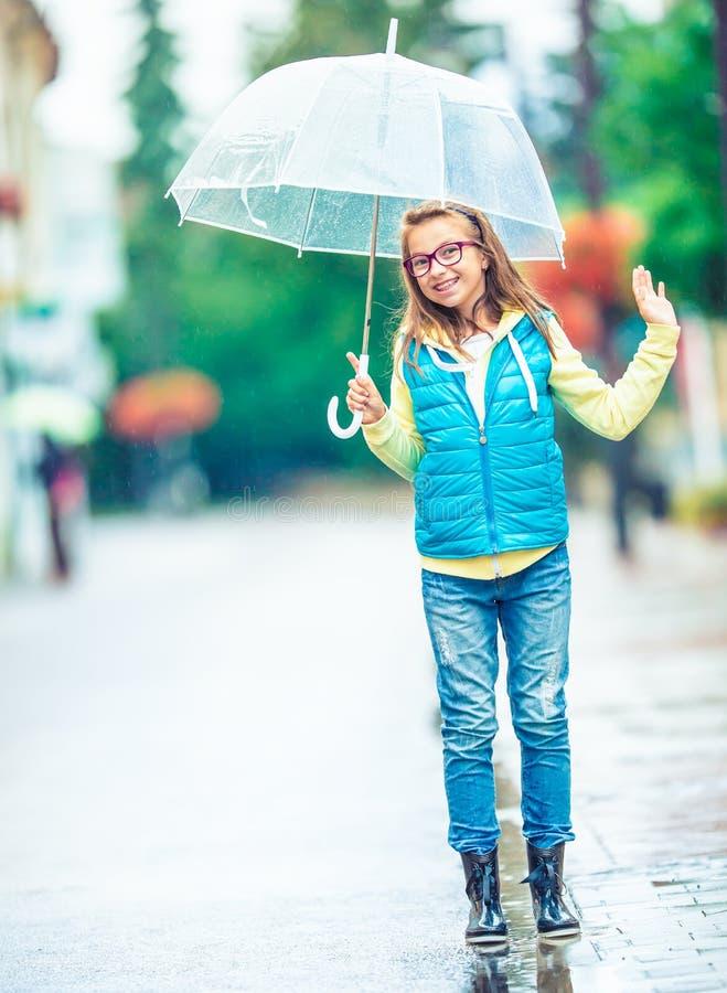 美丽的年轻青春期前的女孩画象有伞的在雨下 库存图片