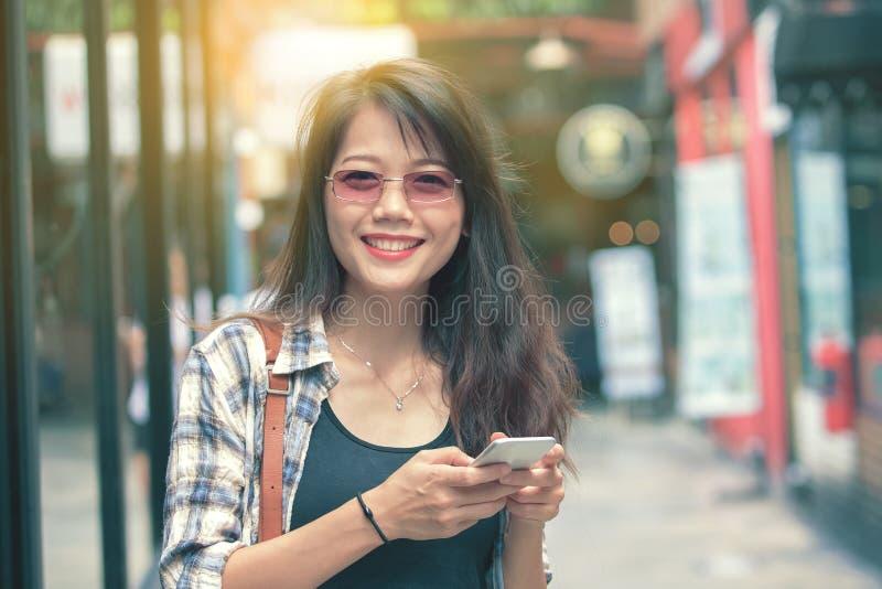美丽的aisan与巧妙的电话的妇女暴牙的微笑的面孔在ha 免版税库存照片