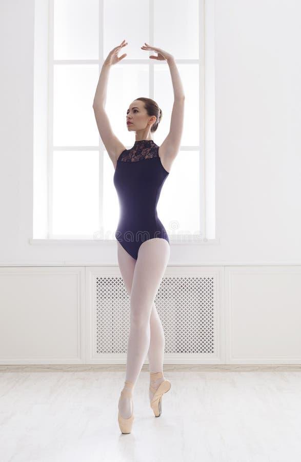 美丽的ballerine在第五个芭蕾位置站立 免版税图库摄影