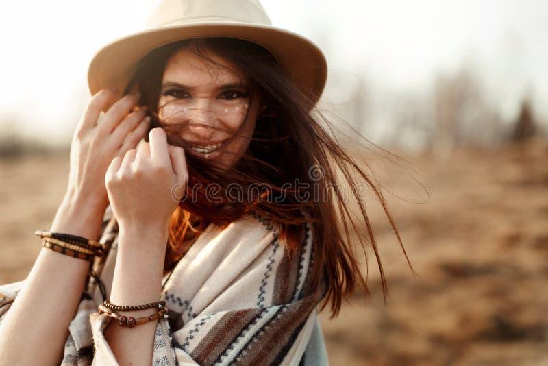 美丽的boho妇女行家,微笑,佩带帽子和雨披在山的日落,真实的情感,文本的空间 库存图片