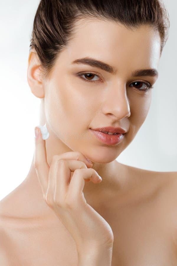 美丽的BOTOX®关心表面面部射入查出s白人妇女 女性申请的奶油和微笑 年轻女人画象有化妆奶油的在皮肤 库存照片