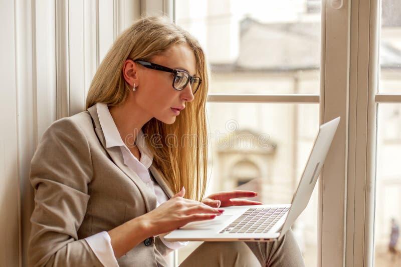 美丽的bussineswoman佩带的玻璃坐与膝上型计算机的窗台在她的手上 库存照片