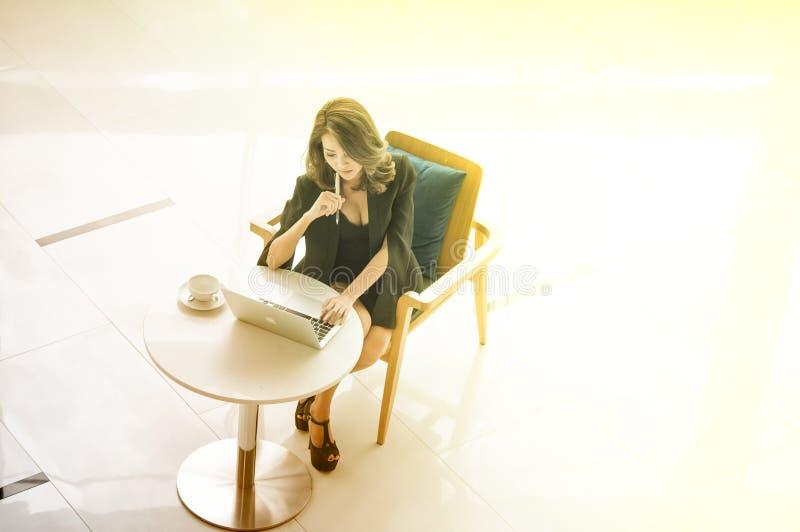 年轻美丽的iAsian女实业家与计算机一起使用在公司中认为成功 免版税库存图片