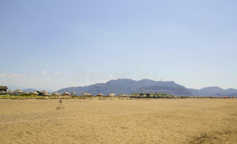 美丽的Iztuzu海滩在土耳其 明亮的太阳发光在宽沙子海岸线 在背景的山 小秸杆 免版税库存图片