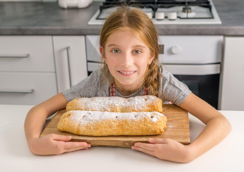 美丽的litte女孩用在桌上的被烘烤的苹果果馅奶酪卷 库存图片