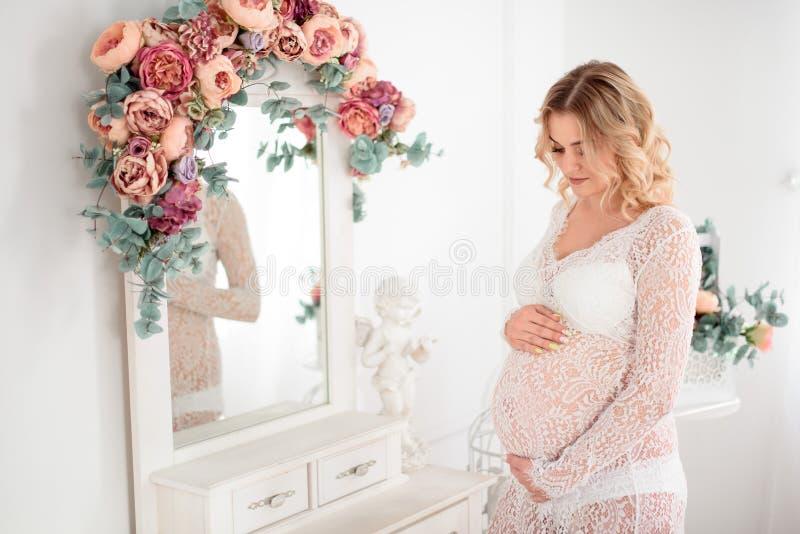 美丽的Pregant白肤金发的妇女在轻的研究中的握他的腹部 库存图片