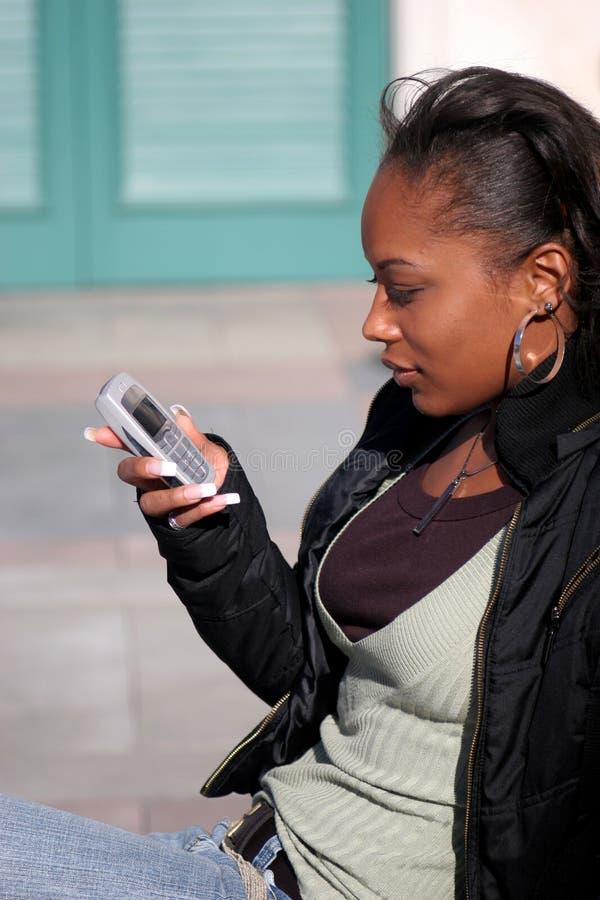美丽的texting的妇女 免版税库存照片