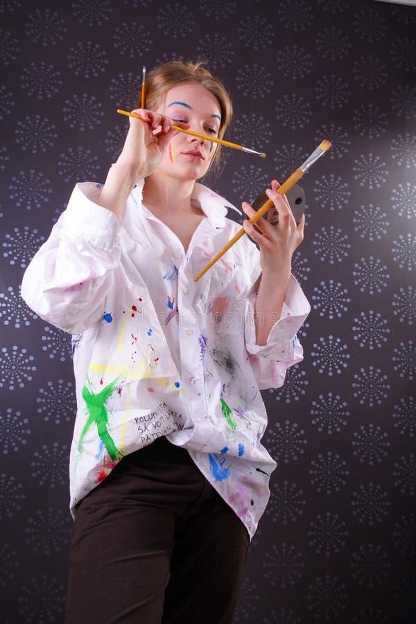 美丽面对她的油漆妇女年轻人 免版税库存图片