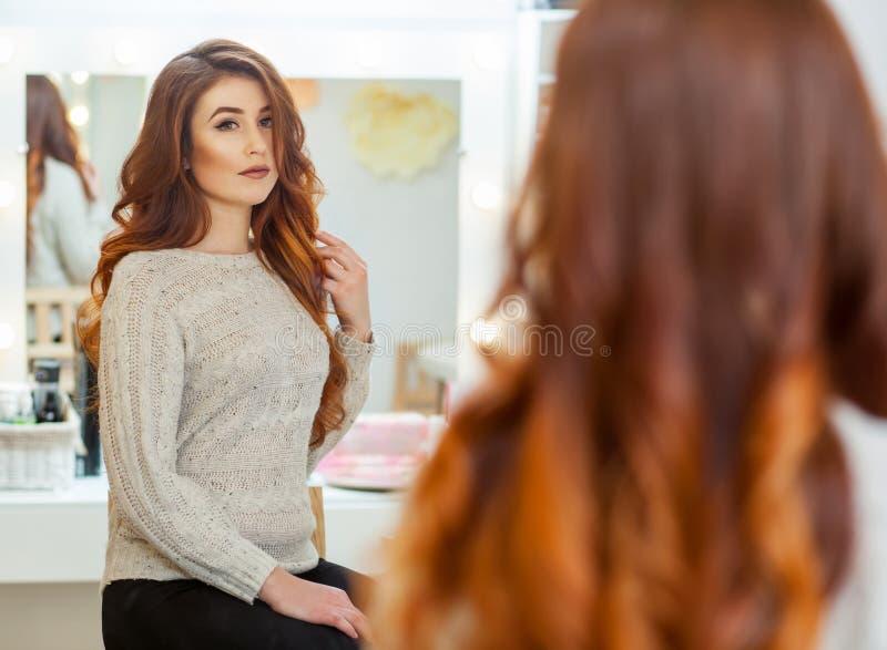 美丽,与长期,红发长毛的女孩在美容院的一个镜子前面坐 免版税库存照片