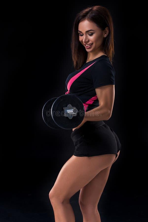 美丽,健康和运动的妇女的适合的身体有的哑铃 摆在运动服的亭亭玉立的妇女 免版税库存照片