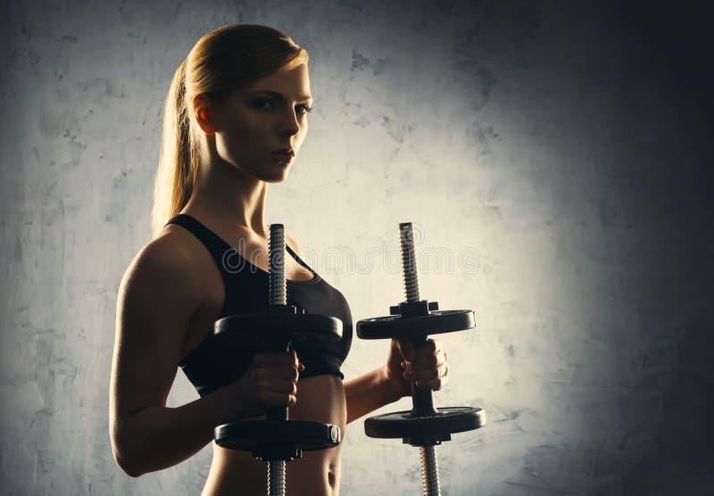 美丽,健康和运动的妇女的适合的身体有的哑铃 摆在运动服的亭亭玉立的妇女 图库摄影