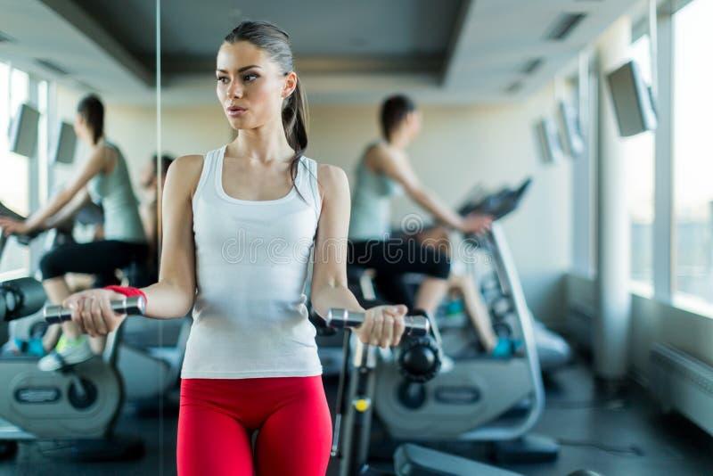 美丽,在健身房的少妇举的重量 图库摄影