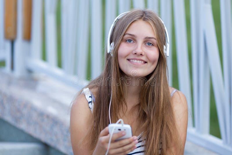 美丽,愉快的女孩画象有智能手机的 免版税图库摄影