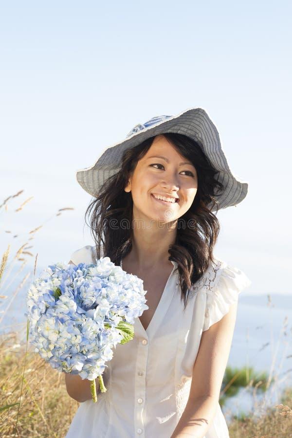 美丽,愉快,健康,微笑,拿着鲜花的年轻亚裔妇女户外在夏天 她穿一件女性礼服 库存图片