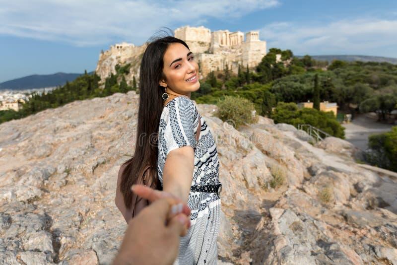 美丽,漂泊样式女孩拉扯她的从手的朋友到雅典卫城,希腊 免版税库存图片