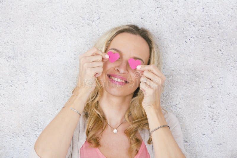 美丽,白肤金发和性感女孩摆在与两桃红色,在灰色,具体背景前面的纸心脏 免版税图库摄影