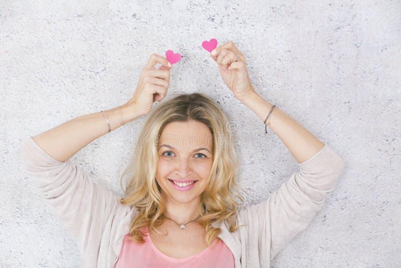 美丽,白肤金发和性感女孩摆在与两桃红色,在灰色,具体背景前面的纸心脏 库存照片