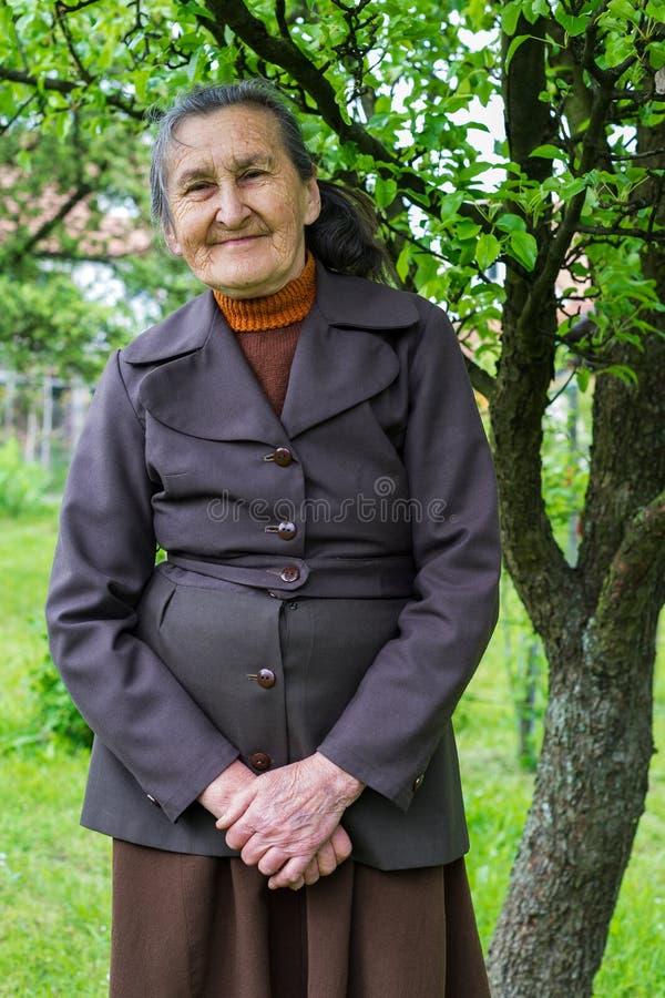 美丽80摆在为一张画象的正岁资深妇女在她的庭院里 库存图片