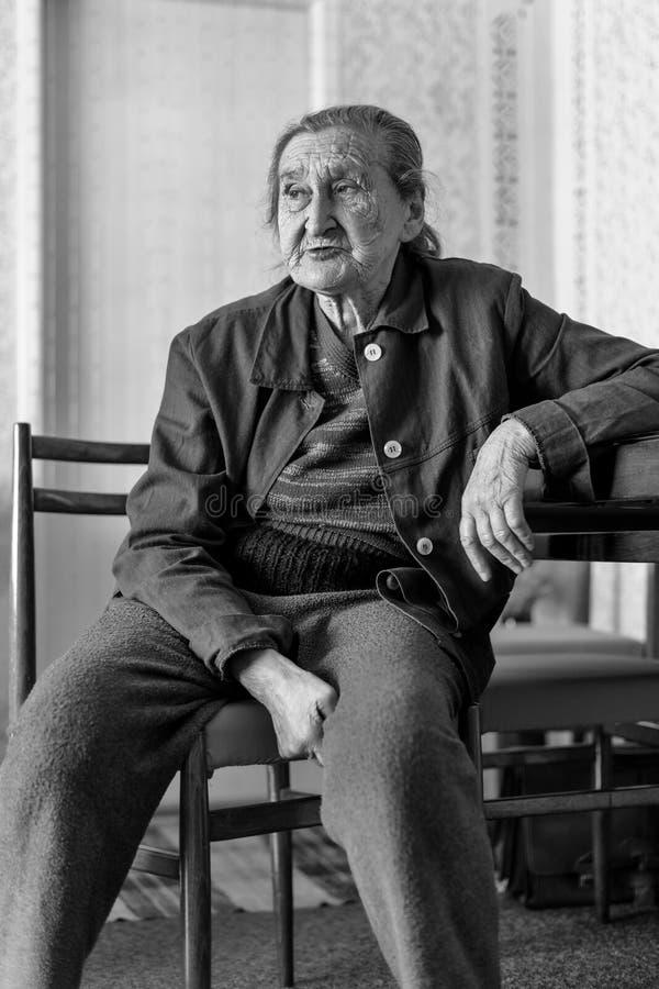 美丽80正岁资深妇女画象 年长妇女的黑白充分的身体图象坐椅子 免版税库存照片