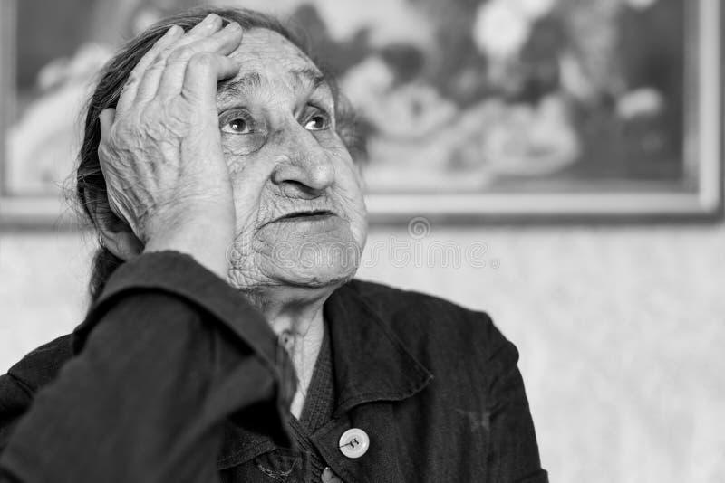 美丽80正岁资深妇女画象 年长担心的妇女的黑白图象坐椅子 库存照片