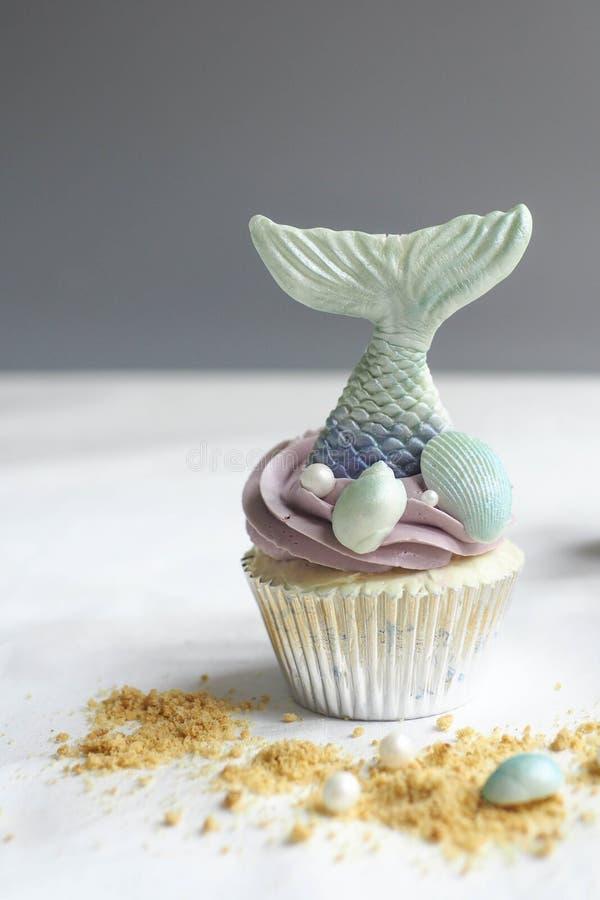 美人鱼杯形蛋糕和沙子 免版税库存图片
