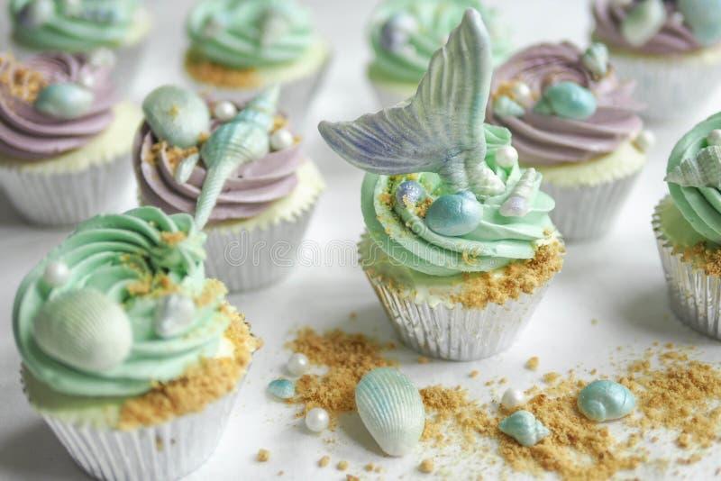 美人鱼杯形蛋糕和沙子 免版税图库摄影