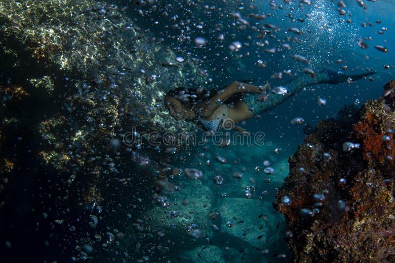 美人鱼游泳的水中在深蓝色海 免版税库存图片