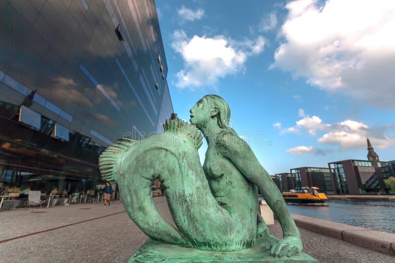 美人鱼铜雕塑在1921年做的哥本哈根的,丹麦 在皇家丹麦图书馆和水之间的妇女形象咆哮 免版税库存图片