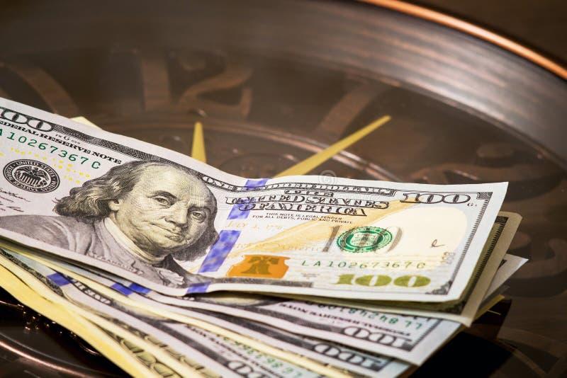 美元在一个大时钟说谎,计数时间 时刻挣钱 时间是money_ 免版税库存图片