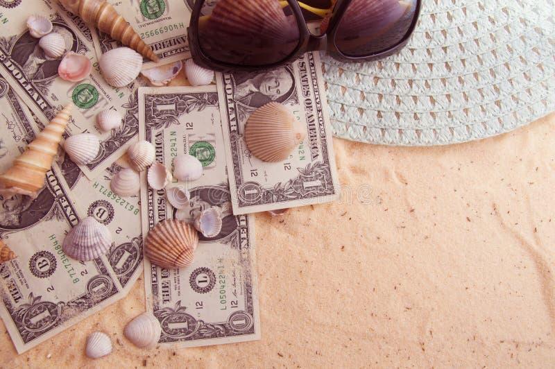 美元在沙子说谎与贝壳和海滩辅助部件一起 免版税图库摄影