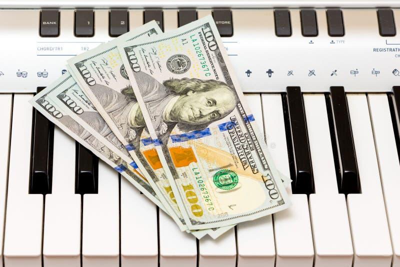 美元在钢琴钥匙说谎 音乐会的付款,从执行音乐works_的赢利 免版税图库摄影