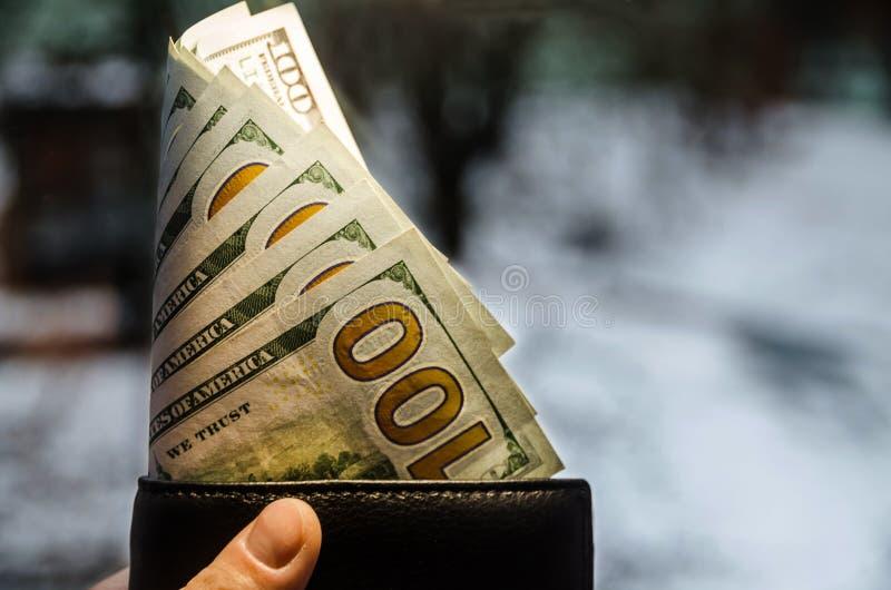 美元在钱包和手里 图库摄影