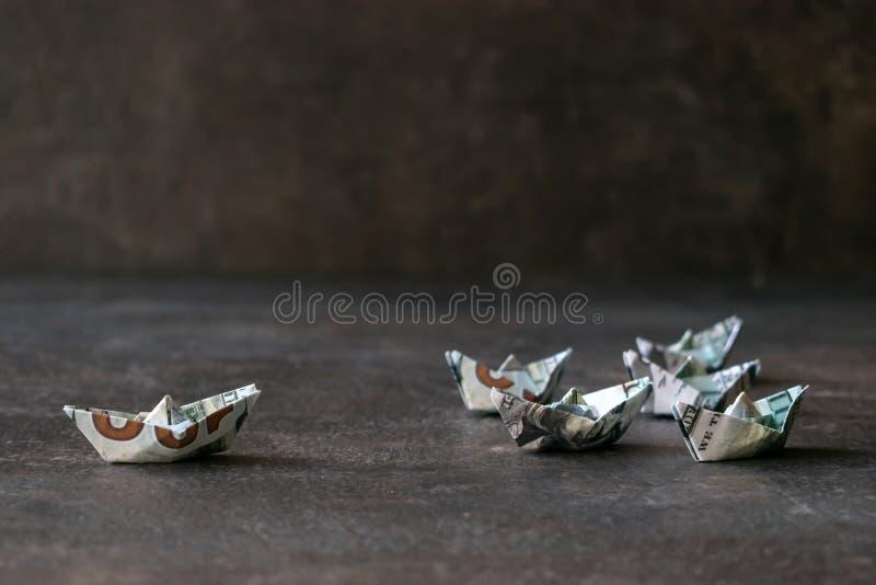 美元在黑暗的背景的纸小船 从金钱的许多船 免版税图库摄影
